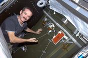 <strong>Chris Hadfield installing Ultra-Sonic Background Noise Test sensors behind a rack in the ISS. These sensors detect high frequency noise levels generated by station hardware and equipment. (NASA)</strong>
