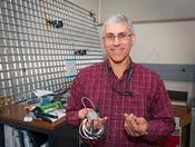 <strong>Eric Madaras, an aerospace technologist for NASA, holds one of the Distributed Impact Detection System units used as part of the Ultrasonic Background Noise Test aboard the ISS. (NASA/Sean Smith)</strong>