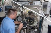 <strong>Astronaut Chris Cassidy installing the right glove on the Microgravity Science Glovebox just before starting a BASS investigation experiment run. Image Credit: NASA</strong>