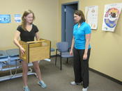 <strong>Lauren Geier, ATC simulates work task of picking up a large item safely.</strong>