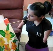 Artist Zuly Sanguino who taught herself to paint, despite being born without limbs, at work on a new canvas.