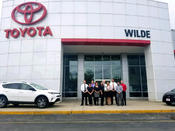 <strong>The Wilde Toyota team stands proudly at the dealership entrance, showcasing their 2017 Best of West Allis Award in the Auto Dealers category.</strong>