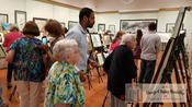 <strong>Guests toured the paintings displayed at The Senior Art Exhibit.</strong>
